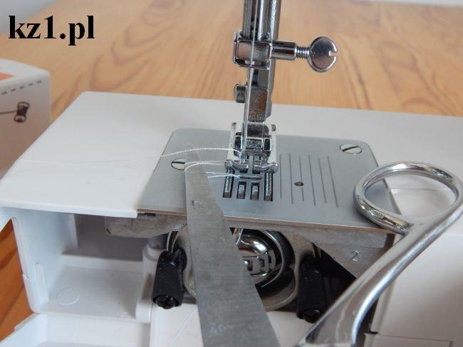 wyciąganie dolnej nitki z bębenka za pomocą nożyczek