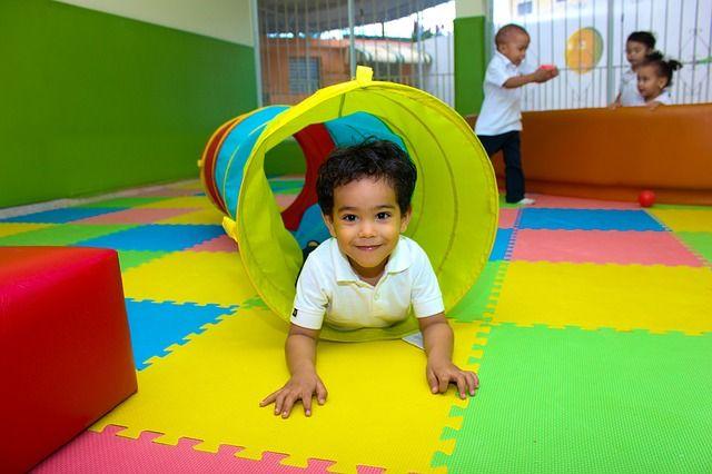 dziecko przechodzące przez tunel do zabaw z materiału