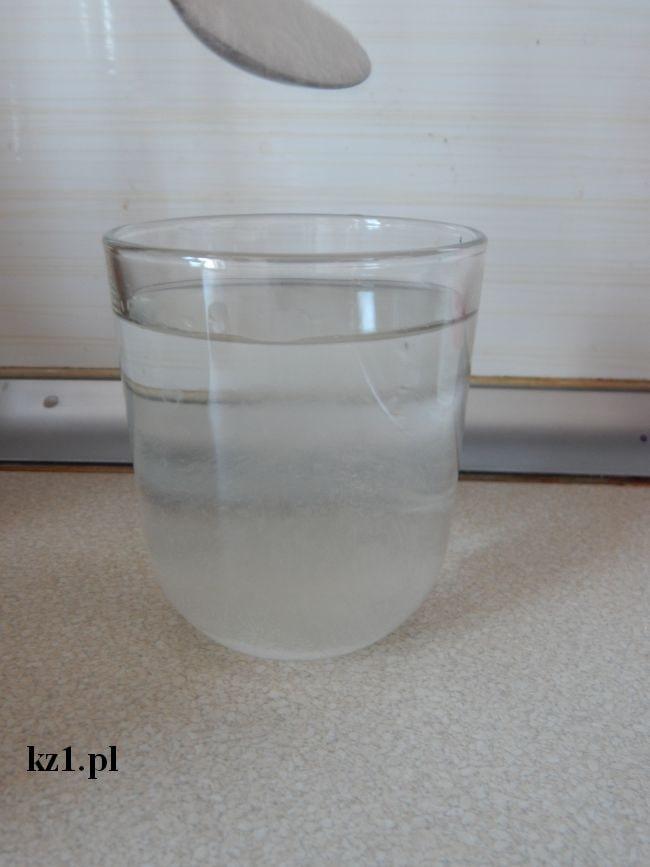 wsypywanie soli do szklanki z wodą