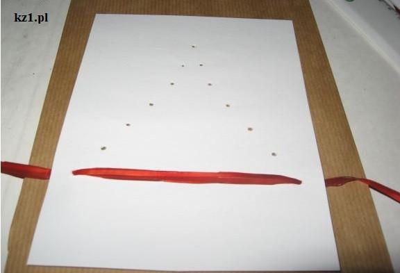 tasiemka przewleczona przez dziurki w kartce